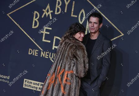 Tom Tykwer (R) and his wife Marie Steinmann (L) wearing a fur coat reading 'Fake' pose during the premiere of the third season of the TV series 'Babylon Berlin' at the Zoo Palast in Berlin, Germany, 16 December 2019. The German crime drama is based on novels by author Volker Kutscher.