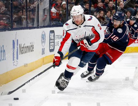 Washington Capitals defenseman Nick Jensen, left, controls the puck in front of Columbus Blue Jackets forward Alexander Wennberg, of Sweden, during the second period of an NHL hockey game in Columbus, Ohio