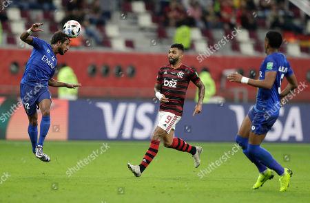 Al Hilal's Yasser Al Shahrani, left, clears the ball in front Flamengo's Gabriel Barbosa during the Club World Cup semifinal soccer match between Flamengo and Al Hilal at the Khalifa International Stadium in Doha, Qatar