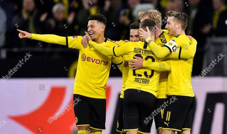 Dortmund's Julian Brandt, center, is celebrated by Dortmund's Jadon Sancho, left, and Dortmund's Marco Reus, right, after he scored his side's second goal during the German Bundesliga soccer match between Borussia Dortmund and RB Leipzig in Dortmund, Germany