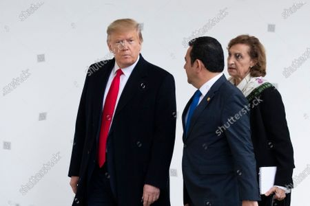 US President Donald Trump (L) listens to President of Guatemala Jimmy Morales (2-R) through a translator (R), as they walk down the Colonnade to hold a meeting in the Oval Office at the White House, in Washington, DC, USA, 17 December 2019. The two leaders are expected to discuss immigration, as curbing undocumented migration has been a main priority of the Trump administration.