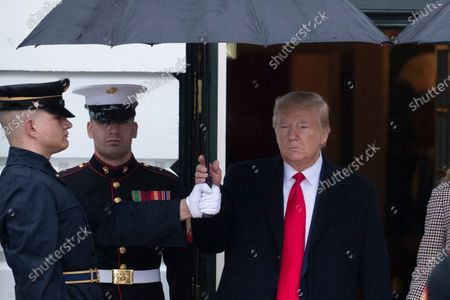 US President Donald Trump (R) grabs an umbrella while walking out to greet President of Guatemala Jimmy Morales and his wife Marroquin Argueta de Morales (both not pictured); at the South Portico of the White House, in Washington, DC, USA, 17 December 2019. The two leaders are expected to discuss immigration, as curbing undocumented migration has been a main priority of the Trump administration.
