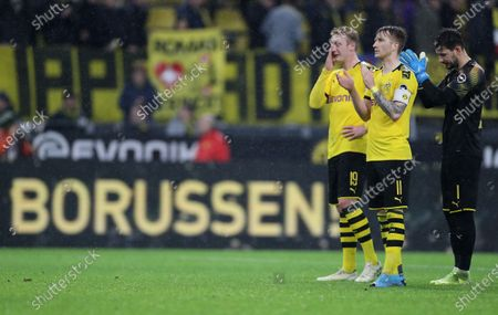 Stock Photo of (L-R) Dortmund's Julian Brandt, Marco Reus and goalkeeper Roman Buerki react after the German Bundesliga soccer match between Borussia Dortmund and RB Leipzig in Dortmund, Germany, 17 December 2019.