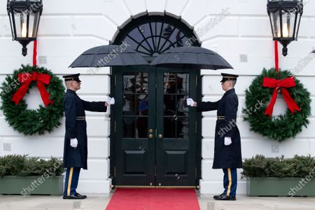 Stock Picture of A US honor guard holds umbrellas outside the South Portico of the White House before US President Donald J. Trump and First Lady Melania Trump come out to greet President of Guatemala Jimmy Morales his wife Marroquin Argueta de Morales; in Washington, DC, USA, 17 December 2019.