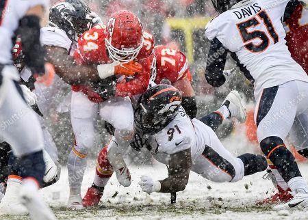 Stock Image of Jonathan Harris, Deyon Sizer, Darwin Thompson. Denver Broncos defensive end Jonathan Harris (92), left, and Denver Broncos defensive tackle Deyon Sizer (91) tackle Kansas City Chiefs running back Darwin Thompson (34) during the first half of an NFL football game in Kansas City, Mo