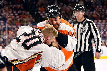 Philadelphia Flyers' Chris Stewart, center, fights Anaheim Ducks' Nicolas Deslauriers during the first period of an NHL hockey game, in Philadelphia