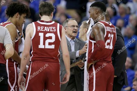 Oklahoma coach Lon Kruger talks to Kristian Doolittle (21) and Austin Reaves (12) during a time out in the second half of an NCAA college basketball game against Creighton in Omaha, Neb