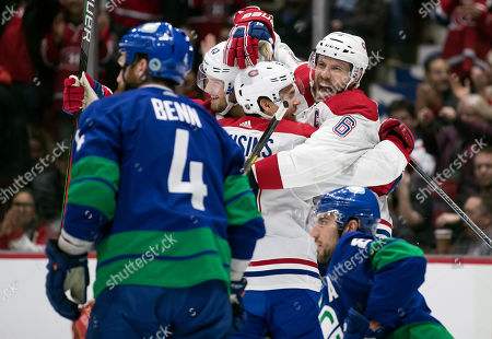 Montreal Canadiens' Shea Weber, back right, Joel Armia, back left, of Finland, and Brett Kulak celebrate Weber's goal as Vancouver Canucks' Jordie Benn (4) and Christopher Tanev (8) look on during the third period of an NHL hockey game, in Vancouver, British Columbia