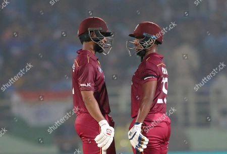 Stock Photo of Shai Hope, Nicholas Pooran. West Indies' Shai Hope, left, and batting partner Nicholas Pooran interact with each other during the second one day international cricket match between India and West Indies in Visakhapatnam, India