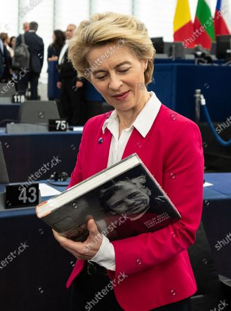 Stock Image of European Commission President Ursula von der Leyen looks at a photo book with Vaclav Havel before a debate at the European Parliament in Strasbourg, France, 18 December 2019. The European Parliament is in plenary session from 16 to 19 December 2019.
