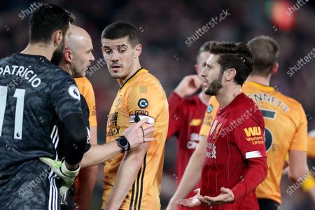 Adam Lallana of Liverpool speaks with referee Anthony Taylor as VAR investigates a possible handball before the goal by Sadio Mane