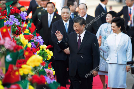 Xi Jinping, Peng Liyuan, Fernando Chui Sai-on, Ho Iat-seng. Chinese President Xi Jinping, front left, and his wife Peng Liyuan, front right, wave after arriving at Macao Airport, followed by the outgoing Macao Chief Executive Fernando Chui Sai-on, second row left, and the newly elected Macao Chief Executive Ho lat-seng, second row center, in Macao, . Xi will attend the 20th anniversary of Macau's return to China