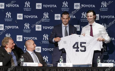 Baseball player Gerrit Cole (R) stands with Yankees manager Aaron Boone as Yankees president Randy Levine (L) and Yankees general manager Brian Cashman (2-L) look on during a press conference introducing Cole as the newest member of the New York Yankees at Yankees Stadium in the Bronx, New York, USA, 18 December 2019. Cole, a pitcher who was with the Houston Astros, joins the Yankees with a nine-year contract worth $324 million/€291 million contract, which is the largest ever contract for a pitcher in baseball.