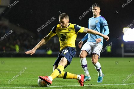 Oxford United forward Jamie Mackie (19) takes a shot at goal during the EFL Cup match between Oxford United and Manchester City at the Kassam Stadium, Oxford