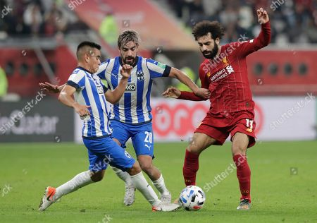 Liverpool's Mohamed Salah fights for the ball with Monterrey's Carlos Rodriguez, left, and Rodolfo Pizarro during the Club World Cup semifinal soccer match between Liverpool and Monterrey at the Khalifa International Stadium in Doha, Qatar