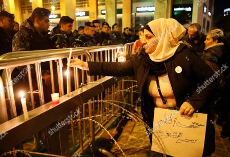 """An anti-government protester holds an Arabic placard that reads:""""You even stole the dram,"""" as she lights a candle in front the riot police, during ongoing protests against the ruling elite of corruption and financial crisis, in downtown Beirut, Lebanon, . Lebanon's caretaker prime minister said Wednesday he's no longer a candidate for the post, eliminating himself from consideration on the eve of scheduled consultations between the president and parliamentary blocs for naming a new premier"""