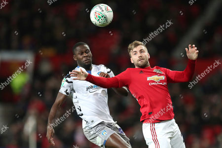 Colchester United's Brandon Comley, left, and Manchester United's Luke Shaw vie for the ball during the English League Cup quarter final soccer match between Manchester United and Colchester United at Old Trafford in Manchester, England
