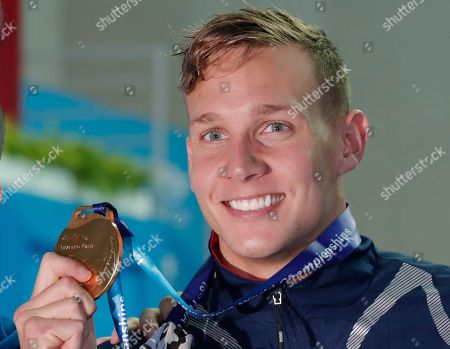 Shows gold medalist United States' Caeleb Dressel posing with his gold medal following the men's 50m freestyle final at the World Swimming Championships in Gwangju, South Korea. In the post-Michael Phelps world, Dressel fits snugly into the successor's slot. Coming off two dynamic performances at the world swimming championships, Dressel figures to be one of the biggest stars at the 2020 Tokyo Games. Yet he is reticent to step into the spotlight