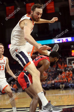 Virginia forward Jay Huff leaps over Stony Brook guard Andrew Garcia (23) during an NCAA college basketball game in Charlottesville, Va