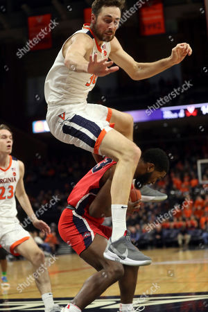 Virginia forward Jay Huff (30) leaps over Stony Brook guard Andrew Garcia (23) during an NCAA college basketball game in Charlottesville, Va