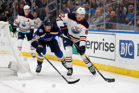 Edmonton Oilers' Caleb Jones (82) passes the puck as St. Louis Blues' Zach Sanford (12) defends during the second period of an NHL hockey game, in St. Louis