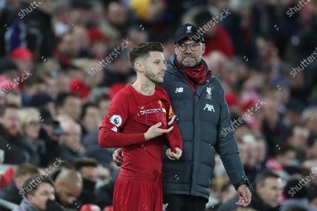 Liverpool Manager Jurgen Klopp  speaks with substitute Adam Lallana