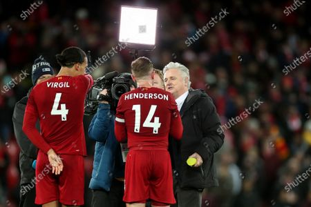 Stock Photo of Virgil van Dijk and Jordan Henderson of Liverpool are interviewed by BT Sport presenter Des Kelly on the pitch at the end of the match