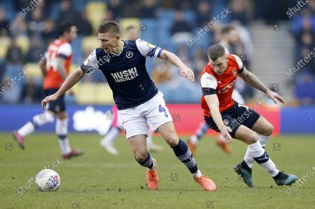 Shaun Hutchinson of Millwall turns away from James Collins of Luton Town