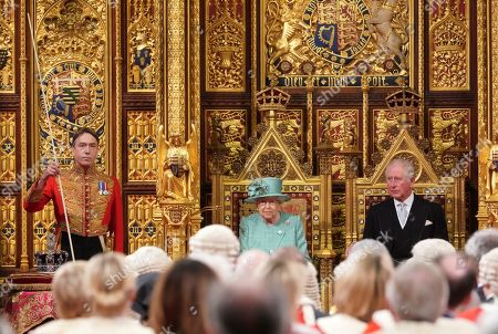 Britain's Queen Elizabeth II takes her seat on the the Sovereign's Throne next to Prince Charles before reading the Queen's Speech during the State Opening of Parliament at the Houses of Parliament