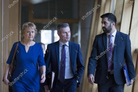 Roseanna Cunningham, Cabinet Secretary for Environment, Climate Change and Land Reform, Derek Mackay, Cabinet Secretary for Finance, Economy and Fair Work, and Humza Yousaf, Cabinet Secretary for Justice, make their way to the Debating Chamber.