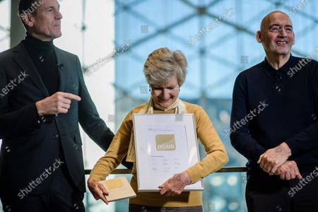 Axel Springer Supervisory Board Vice Chairwoman Friede Springer (C) holds a certificate and a plaque for 'sustainable building' next to Axel Springer CEO Mathias Doepfner (L) and Dutch architect Rem Koolhaas (R) during a hand-over of keys ceremony at the new Axel Springer building in Berlin, Germany, 19 December 2019. The construction of the new building, an architectural draft of Dutch architect Rem Kolhaas, started three ago in October 2016. From spring 2020 various parts of the Axel Springer publishing house, amongst them the WELT newspaper, shall reside in the new complex.