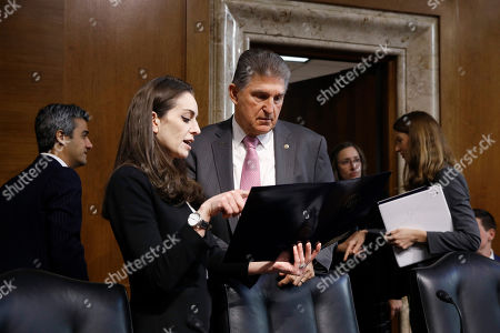 Sen. Joe Manchin, D-W.Va., center, ranking member of the Senate Energy and Natural Resources Committee, speaks with a member of his staff before a hearing on the impact of wildfires on electric grid reliability, on Capitol Hill in Washington