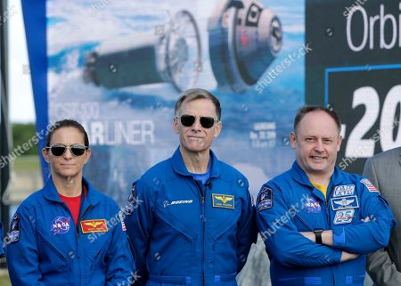 NASA astronaut Nicole Mann, left, Boeing astronaut Chris Ferguson, center, and NASA astronaut Mike Fincke stand in front of the countdown clock during a press conference at the Kennedy Space Center, in Cape Canaveral, Fla., . They will be the first crew to fly on the Starliner spacecraft some time next year