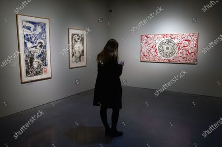 A journalist looking her mobile phone next to paintings and drawings during the exhibition