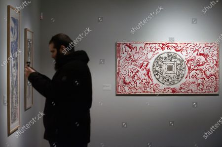 A cameraman recording images of paintings and drawings during the exhibition