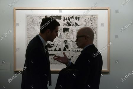 Men talking to each other next to a painting during the exhibition