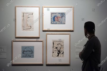 Stock Photo of A worker looking at paintings and drawings during the exhibition