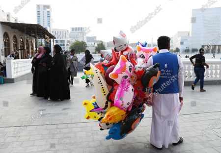 A man sells balloons of cartoon characters alongside one with the face of Sheikh Tamim bin Hamad Al Thani on
