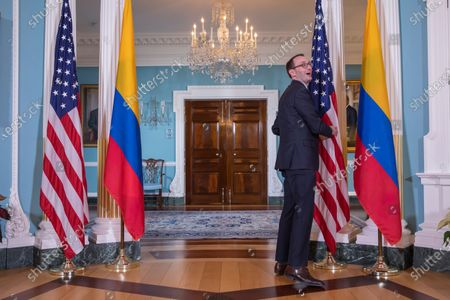 A protocol aide fixes the US and Colombian flags before US Secretary of State Mike Pompeo meets with Colombian Foreign Minister Claudia Blum at the State Department in Washington, DC, USA, 19 December 2019.
