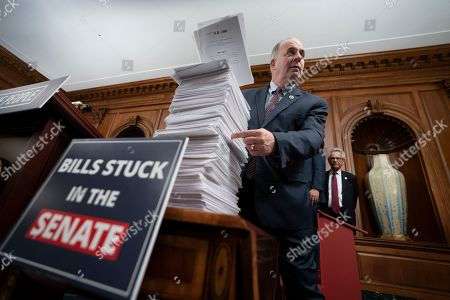 """Rep. Dan Kildee, D-Mich., looks at a stack of bills passed by the Democratic-controlled House of Representatives which have died in the Senate, at the Capitol in Washington, . The Democrats had gathered for Speaker of the House Nancy Pelosi, D-Calif., to call attention to her """"For The People"""" legislative agenda"""