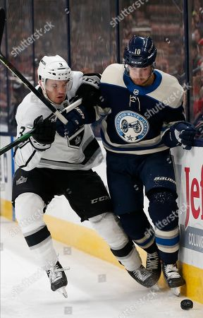 Los Angeles Kings' Matt Roy, left, and Columbus Blue Jackets' Alexander Wennberg, of Sweden, fight for the puck during the second period of an NHL hockey game, in Columbus, Ohio