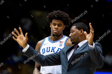Duke's Vernon Carey Jr., left, speaks with Associate Head Coach Nate James, right, during halftime of an NCAA college basketball game against Wofford in Durham, N.C