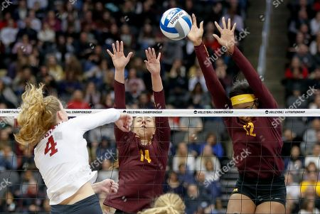 Stanford's Meghan McClure (4) has a shot blocked by Minnesota's Taylor Morgan (12) as she goes up with Kylie Miller, center, during the semifinals of the NCAA Division I women's volleyball championships, in Pittsburgh