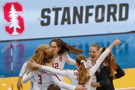 Stanford's Audriana Fitzmorris (12) and Holly Campbell (3) celebrate with teammates after Stanford defeated Minnesota in the semifinals of the NCAA Division I women's volleyball championships, in Pittsburgh. Stanford will face Wisconsin in the championship match Saturday