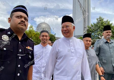 Former Malaysian Prime Minister Najib Tun Razak, center, leaves a mosque in Kuala Lumpur on. Najib made a religious oath in a mosque Friday denying a new accusation that he ordered the killing of a Mongolian woman 13 years ago