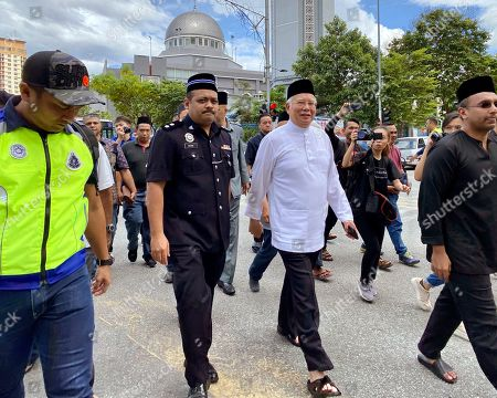 Former Malaysian Prime Minister Najib Tun Razak, center right, leaves a mosque in Kuala Lumpur on. Najib made a religious oath in a mosque Friday denying a new accusation that he ordered the killing of a Mongolian woman 13 years ago