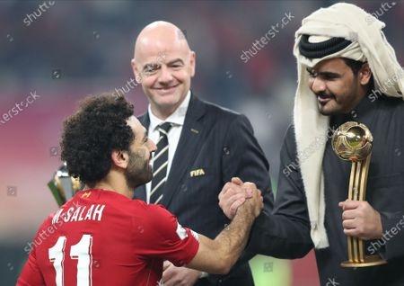 Mohamed Salah (L) of Liverpool FC receives the trophy of best player from Sheikh Joaan bin Hamad bin Khalifa Al Thani (R) after the FIFA Club World Cup final soccer match between Liverpool FC and CR Flamengo in Doha, Qatar, 21 December 2019 as FIFA president Gianni Infantino (C) looks on.