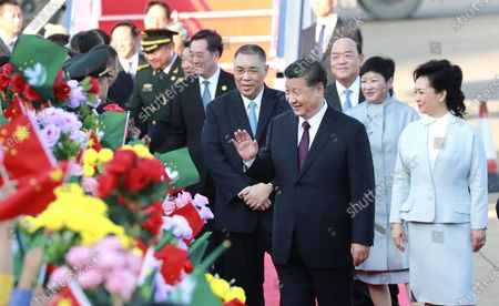 Stock Image of Chinese President Xi Jinping, also general secretary of the Communist Party of China Central Committee and chairman of the Central Military Commission, and his wife Peng Liyuan greet the welcoming crowd after landing at Macao International Airport in Macao, south China