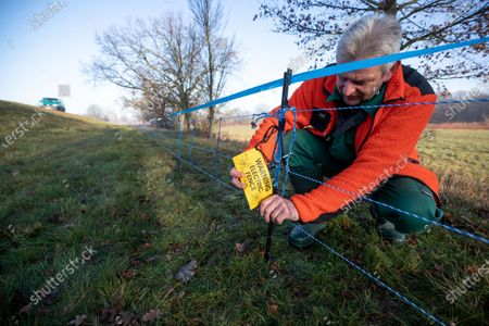 A forest worker Michael Wolff attaches a note reading 'Warning electric fence' on an electric wildlife fence on the border between eastern Germany and western Poland in Guben, Brandenburg, Germany, 20 December 2019. The German state of Brandenburg, in close coordination with the districts, has build a temporary electric wildlife fence to prevent wild boars to cross the Germany from Poland, as the risk of the African Swine Fever (ASF) from infected animals is getting higher.