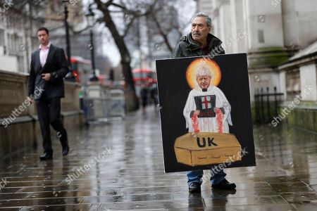 Artist Kaya Mar displays a painting of Britain's Prime Minister Boris Johnson in Westminster in London, . British lawmakers are set to hold their first major vote on Prime Minister Boris Johnson's Brexit bill. It is all but certain to be approved by the country's new Conservative-dominated Parliament on Friday